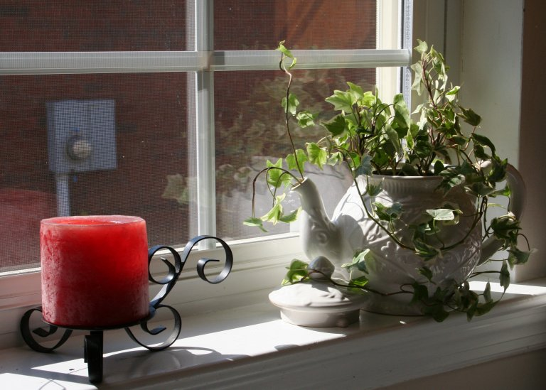 Beautiful white teapot planter with ivy plant sitting on a window sill next to a red candle on a black candle holder