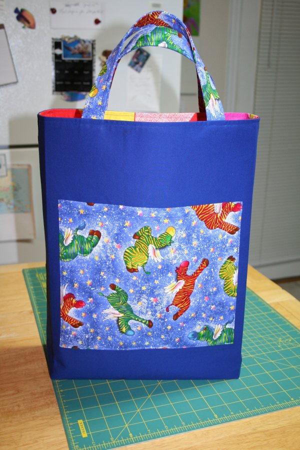 This is the front of the tote bag with a pocket to hold a stuffed toy.