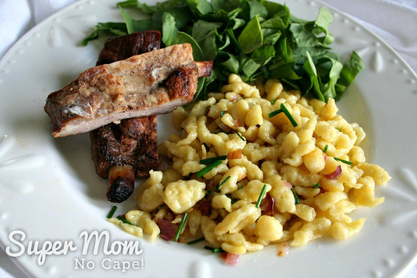 Spaetzle with chives and red onion served with ribs and spinach salad