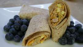 Homemade Breakfast Burrito and fresh blueberries served on a white plate