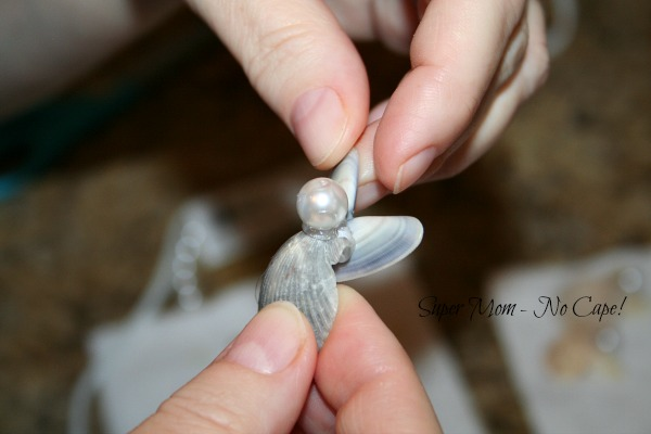 Position clam shells to form the wings of the angel.