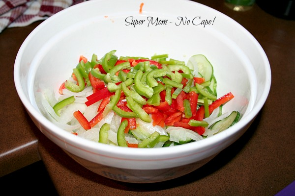 Add peppers and onions to the drained cucumbers.