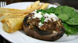 Lamb Stuffed Portobello Mushroom with Feta Cheese on a white plate with parsnip spears and salad