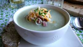 Photo of a Bowl of potato soup garnished with chopped ham, grated cheese and chives