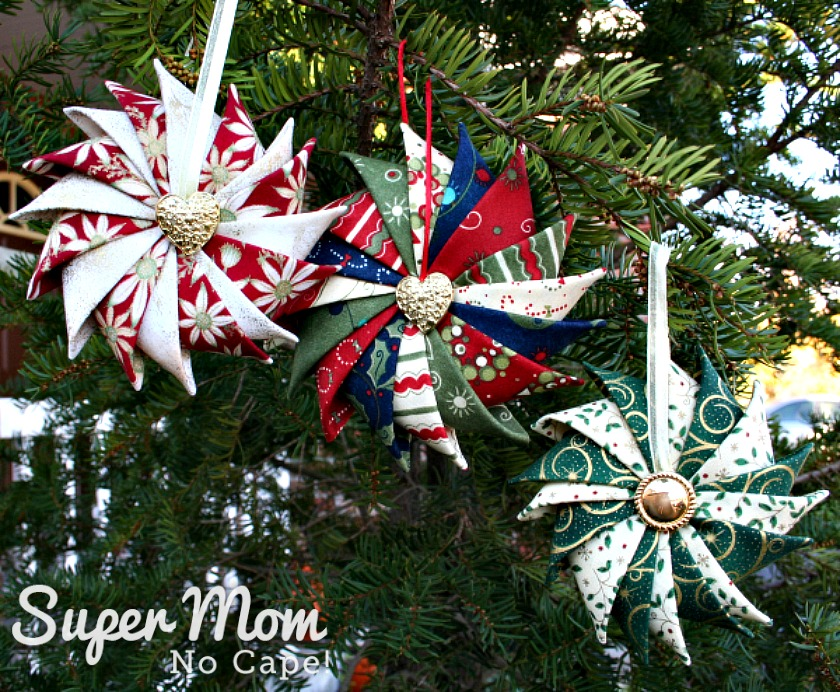 Three Prairie Point Star Ornaments hanging on a pine tree
