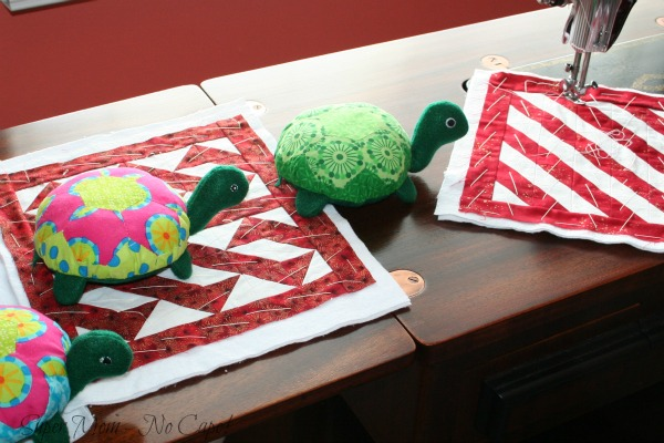 Turtles watching while their quilts are being quilted.