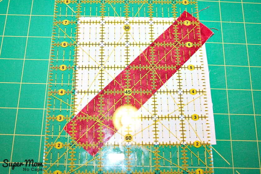 Maple Leaf Blocks - Step 6E Line up the rule on the ironed crease and square up the blocks to 4 and a half inches