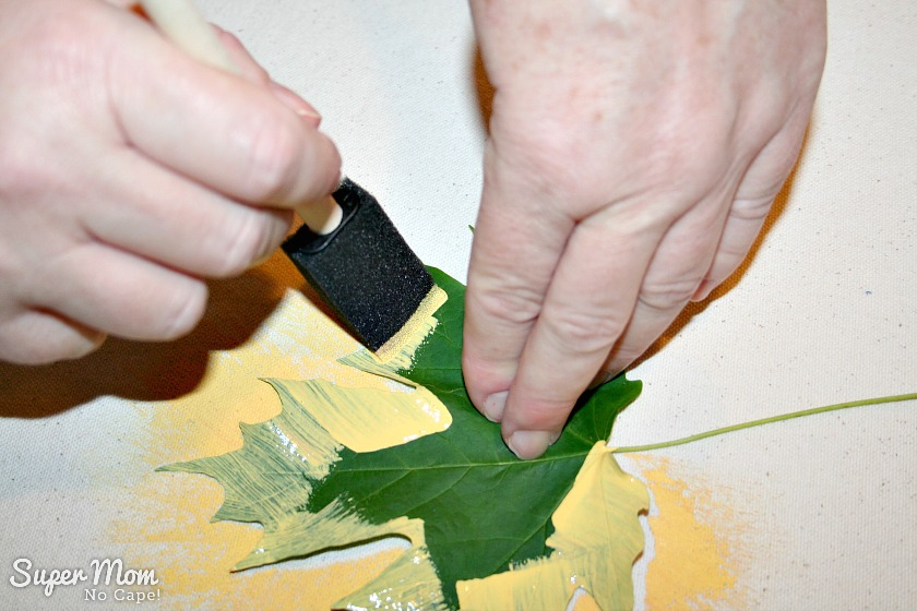 Step 1: One hand holding a leaf in place while yellow paint is being applied to the table runner using a sponge brush