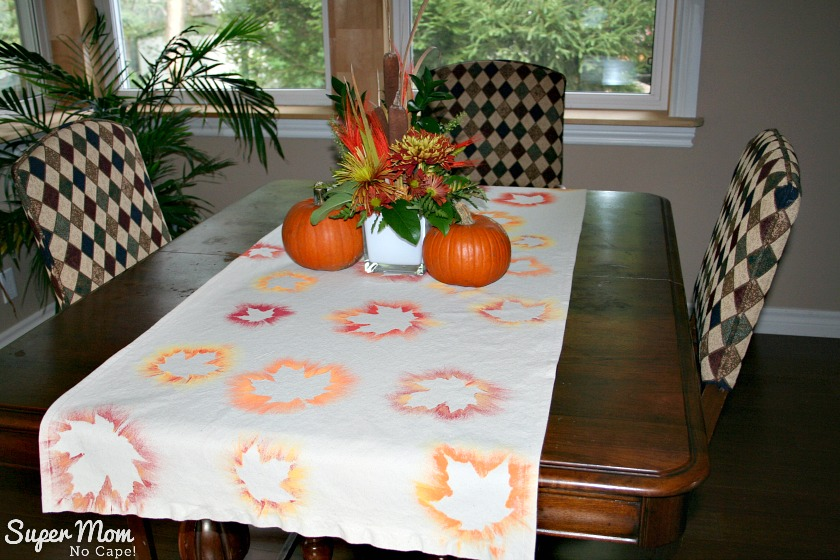 Painted Maple Leaf Table Runner Tutorial displayed on the dining room table with a centerpiece of 2 pumpkins and a floral arrangement