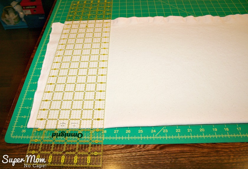 Ruler lined up to cut canvas to the desired width for the Painted Maple Leaf Table runner plus seam allowance