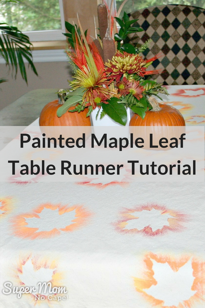 Painted Maple Leaf Table Runner on a table with two pumpkins and a vase of flowers in the center