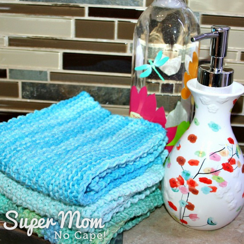 Three knitted seed stitch dishclothes in varying shades of blue stacked beside a white floral soap dispenser and clear dish soap bottle