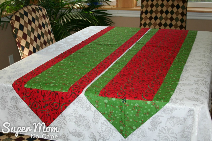 Christmas one hour table runners in red and green fabrics displayed on a white tablecloth