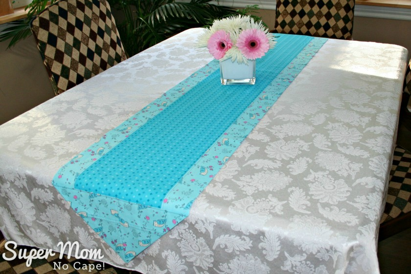 One hour table runner with the owl fabric as the border with the blue fabric in the center displayed on a white tablecloth