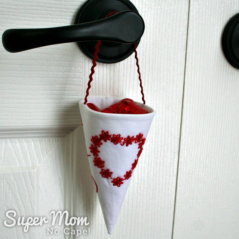 White Fabric Treat Cone with red embroidered floral heart hanging on a black door knob on a white door