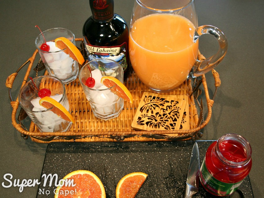 Mai Tai mix in a pitcher with glasses filled with ice and garnished with orange slices and cherries on a wicker serving tray