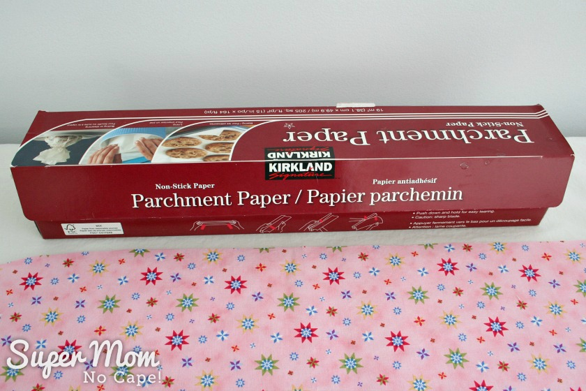 Photo of a box of parchment paper sitting on the pressing station with the outer pattern piece for the Tablet Pouch in the foreground