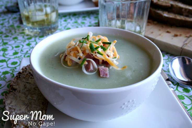 Bowl of potato soup garnished with chopped ham, grated cheese and chives
