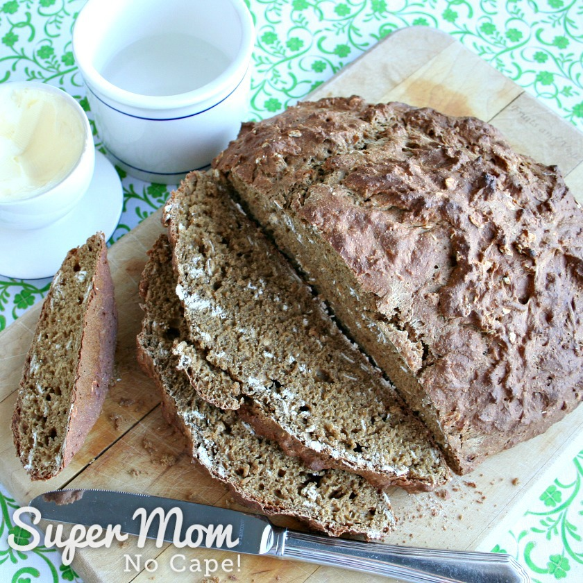 Fresh baked Irish Soda Bread with a Rye Twist on a cutting board with butter bell beside it