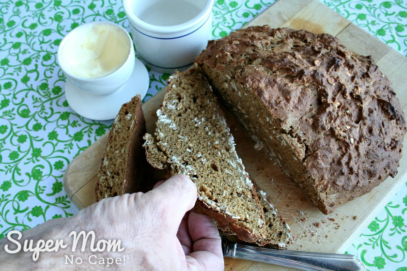 Hand reaching in to take a piece of Irish Soda Bread with a Rye Twist