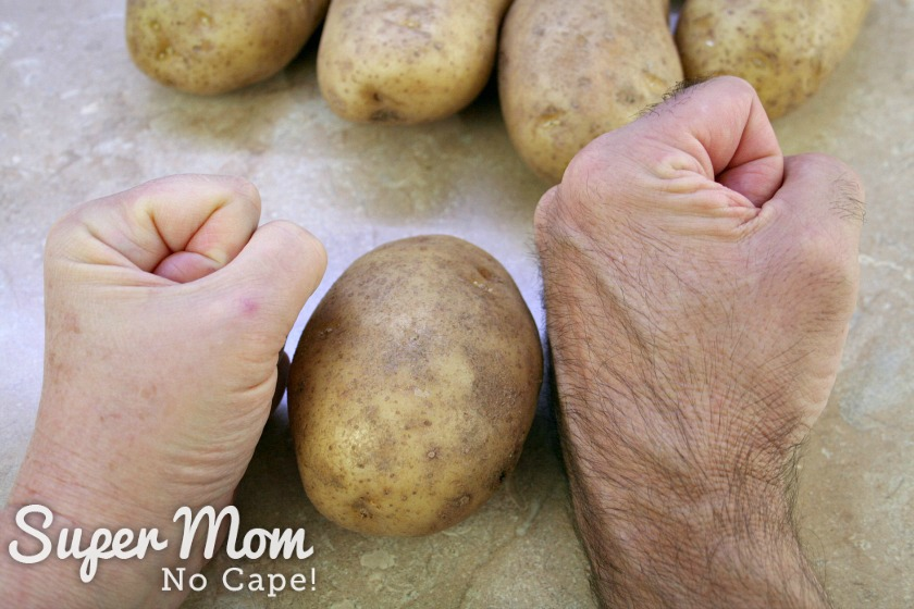 Photo of a woman's fist and a man's fist with potato in between