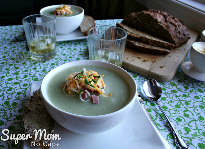 Photo of two servings of Luck of the Irish Potato Soup on a table with a bread board with a loaf of homemade bread