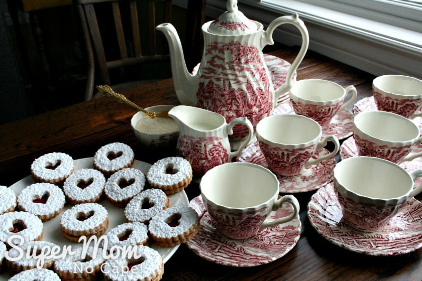 Photo of the party table with pink and white tea set of tea pot, tea cups and saucers and white plate with Snow Storm Linzer Cookies
