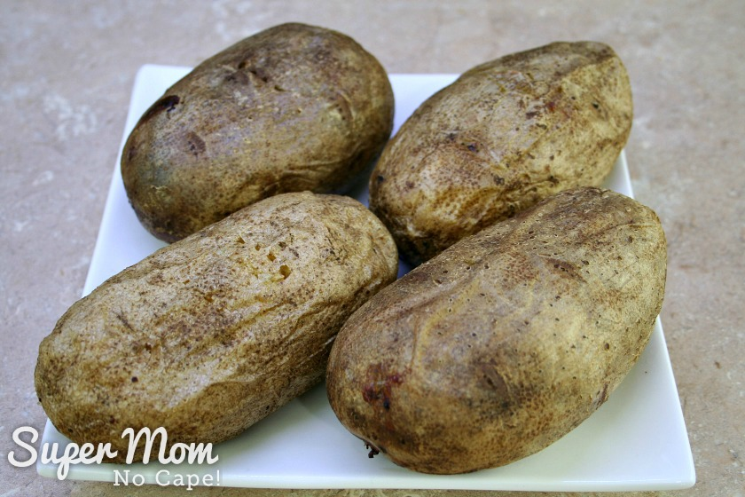 4 baked potatoes cooling on a white plate to make Twice Baked Potatoes