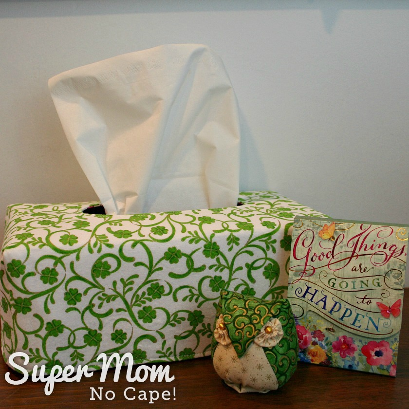 Clover fabric reversible tissue box cover on desk in office with a small owl pincushion and a note book