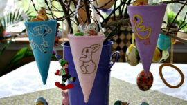 3 Embroidered Fabric Cones with Easter motifs of a lamb, bunny and ducklings handing on a tree branch