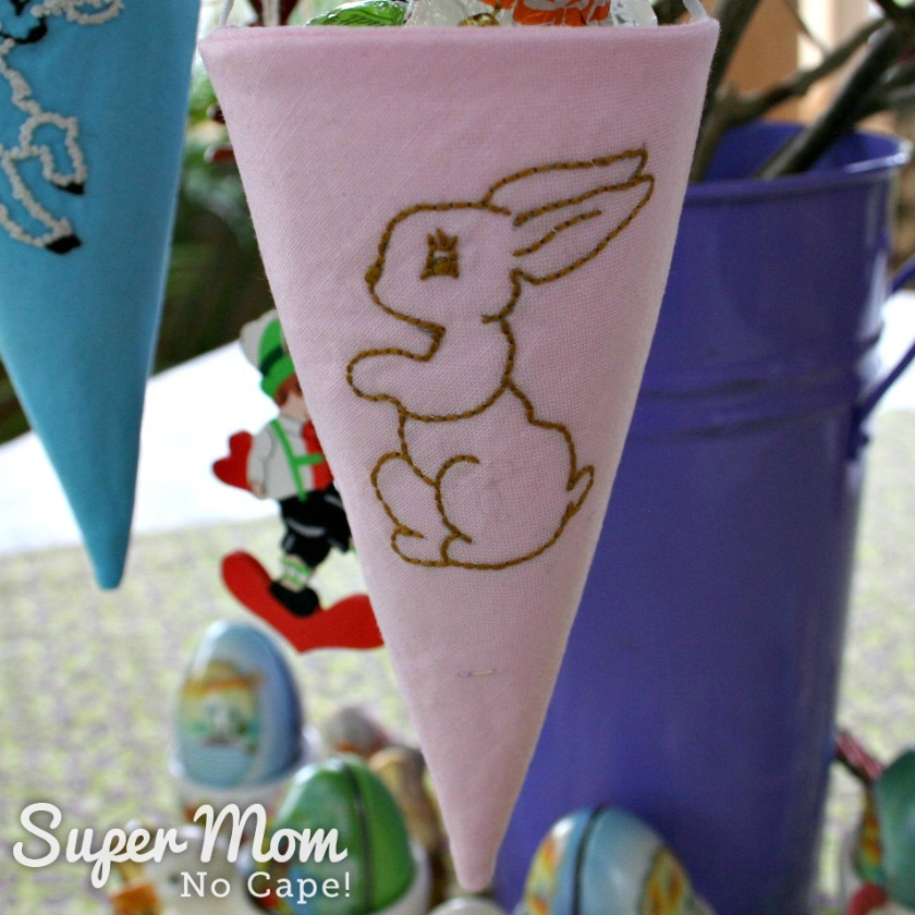 Fabric cone embroidered with a brown bunny.