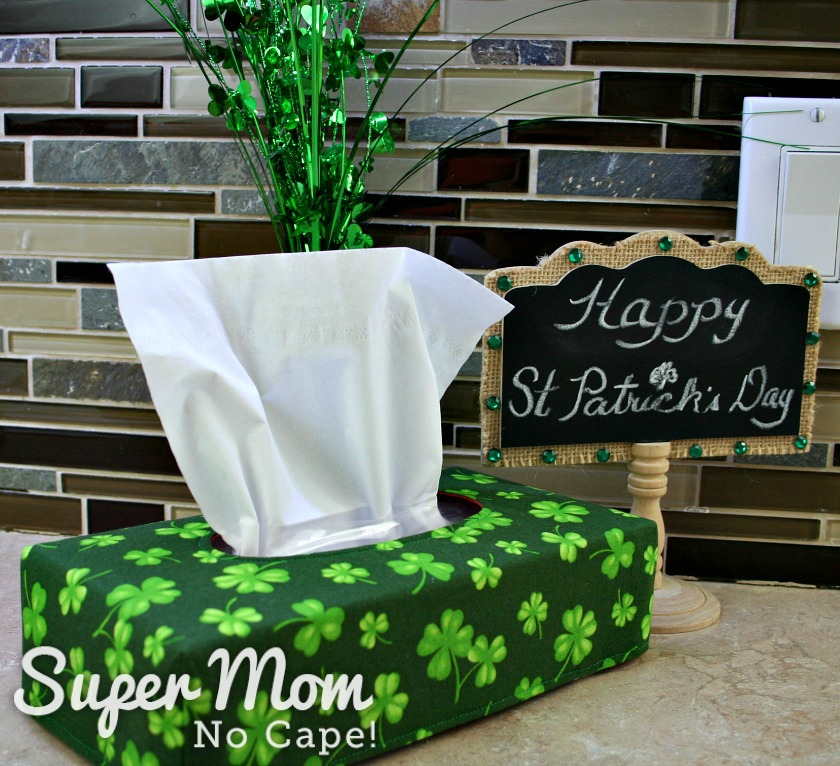 Shamrock fabric reversible tissue box cover on kitchen counter beside a Happy St. Patrick's Day sign and decoration