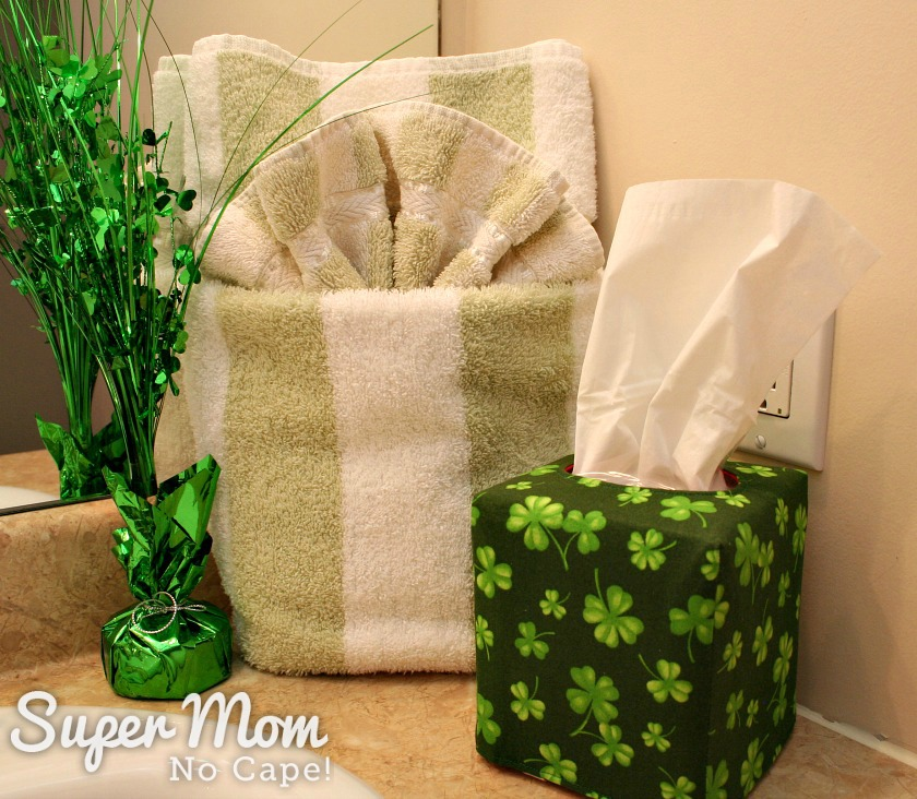 Tall tissue box cover made with shamrock fabric sitting on washroom counter in front of a folded towel