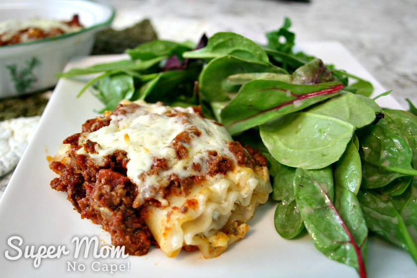 Lasagna Roll Up on white plate with mixed green salad