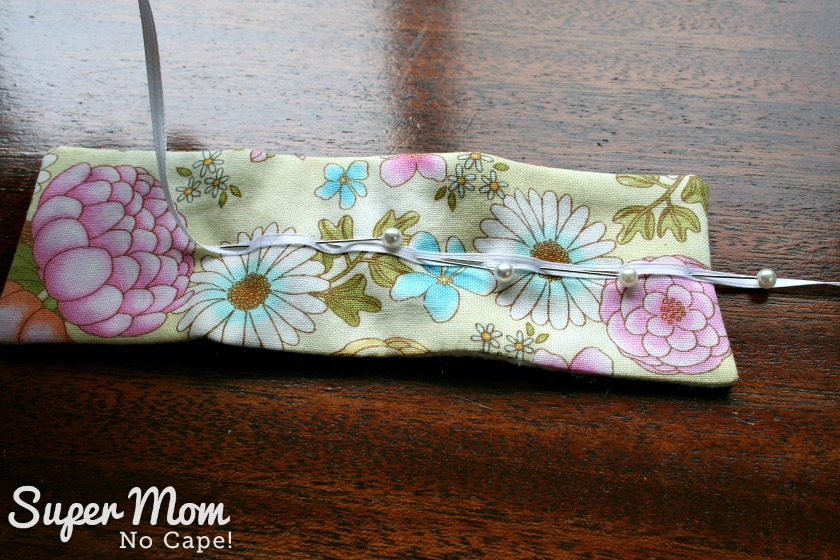 Narrow white ribbon pinned to outside of needle book for Glasses Case Sewing Kit