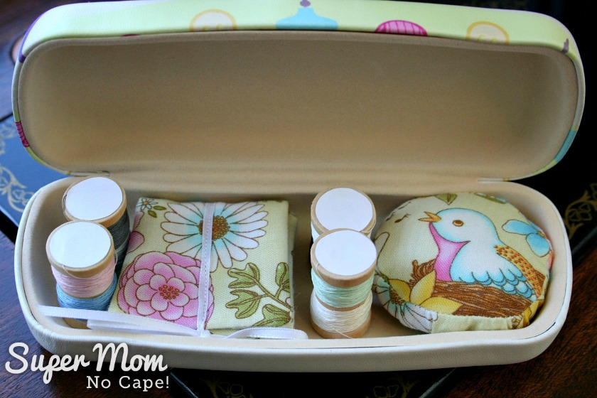 Miniature spools of thread, needle book and pincushion inside Glasses Case Sewing Kit