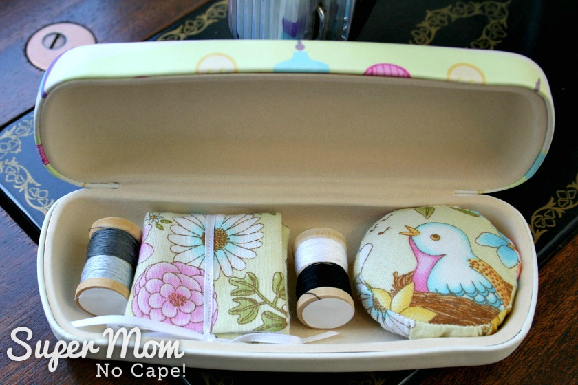 Two miniature thread spools, needle book and pincushion inside Glasses Case Sewing Kit