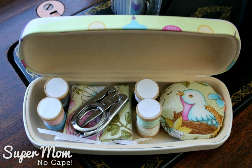 Two miniature thread spools, needle book, pincushion and folding scissors inside Glasses Case Sewing Kit