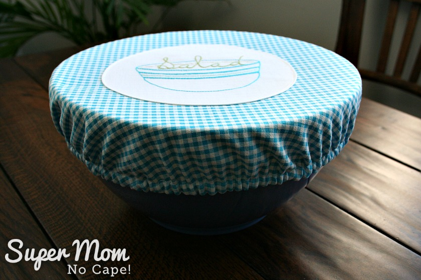 Fabric bowl cover with salad bowl embroidery appliqued to the center