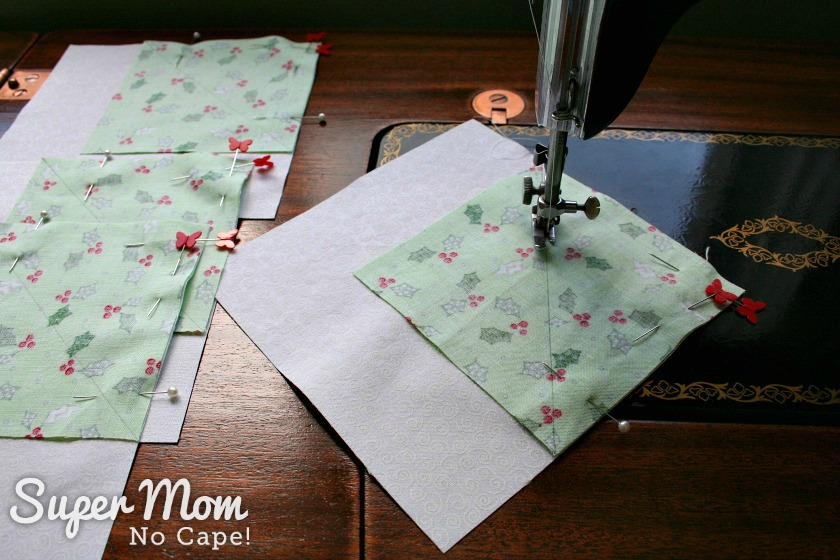 Sewing larger green squares to the corner of the white squares