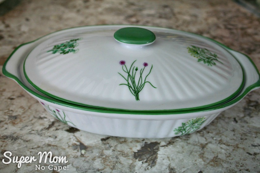 Pretty white casserole dish decorated with herbs with lid on