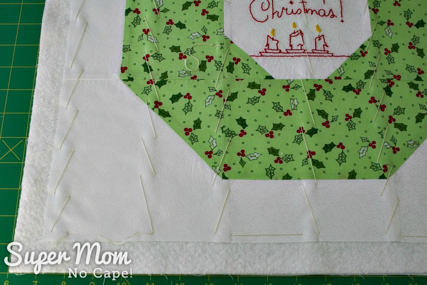 Close up of hand basting on Christmas Wreath Pillow cover front
