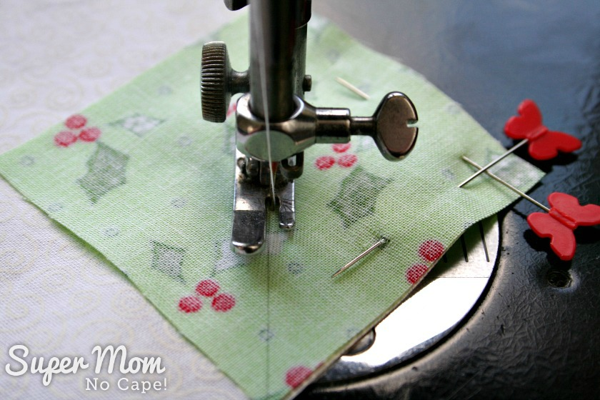 Sewing the green square to the corner of the larger white square