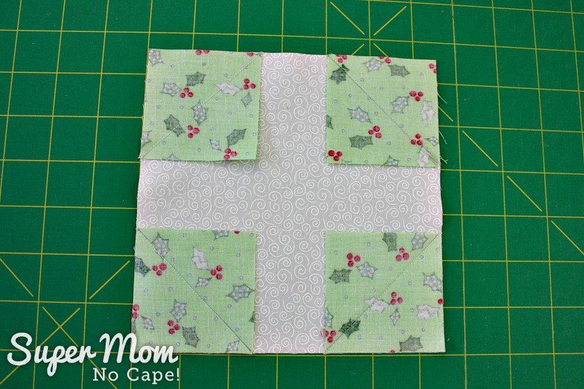 Center block for the Christmas Wreath Pillow Cover with green corners sewn on before trimming