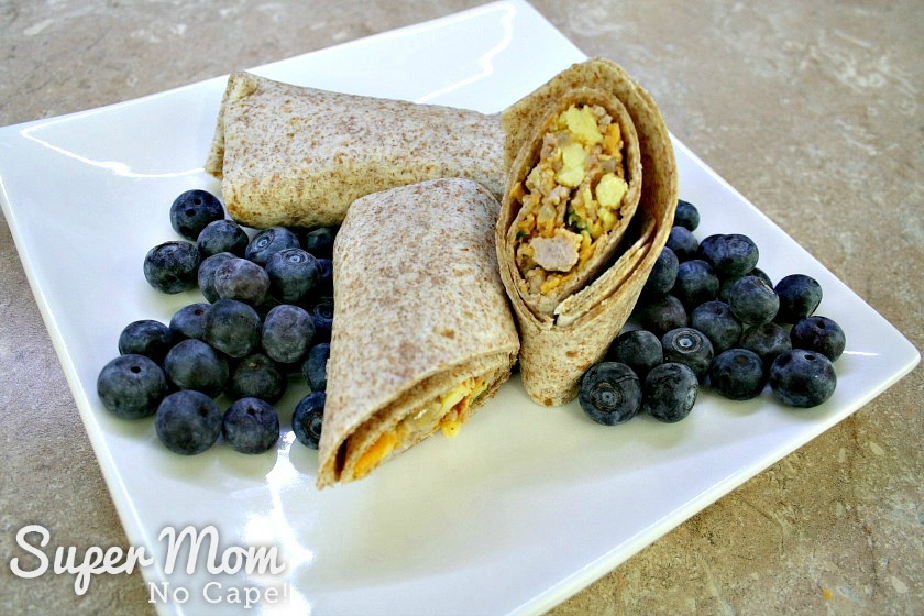 Breakfast burritos served on a white plate with blueberries