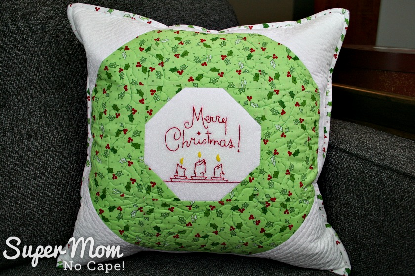 Christmas Wreath Pillow sitting on couch