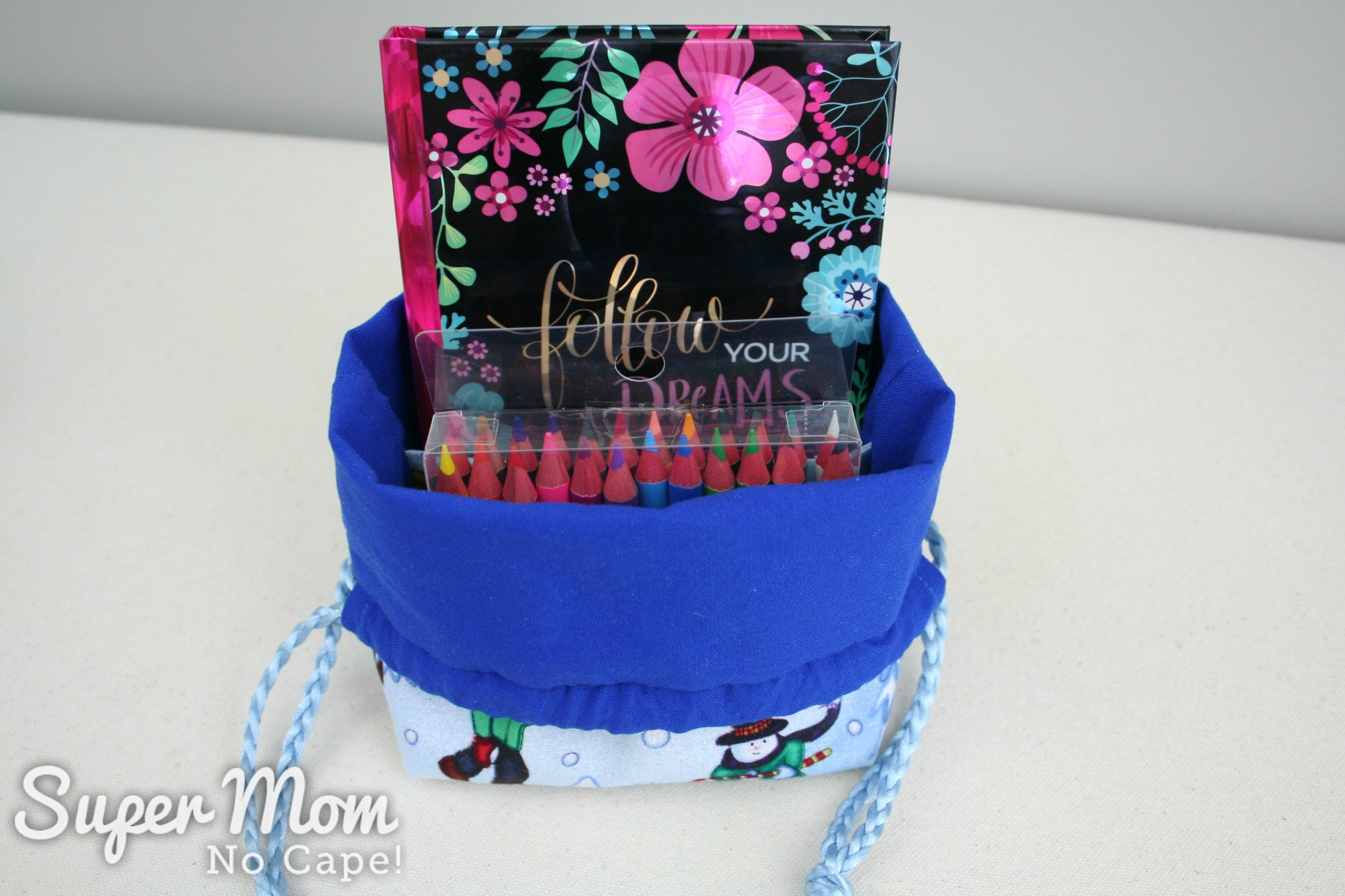 Drawstring gift bag with journal and pencil crayons