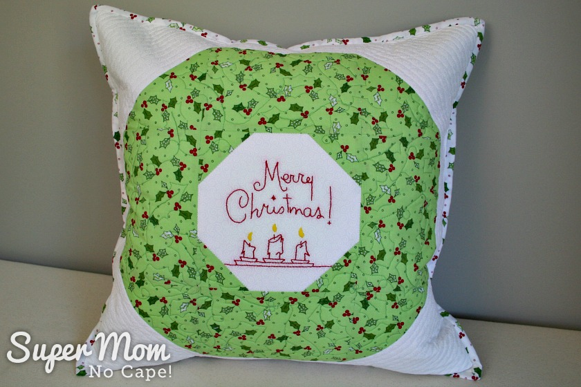 Finished Quilted Christmas Wreath Pillow Cover sitting on a bench