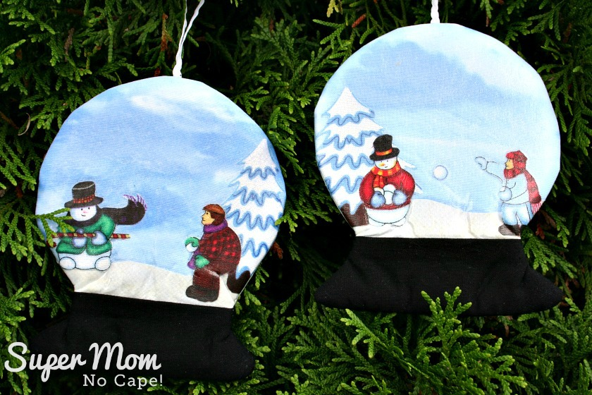 Opposite sides of snowglobes with snowmen and children having snowball fight