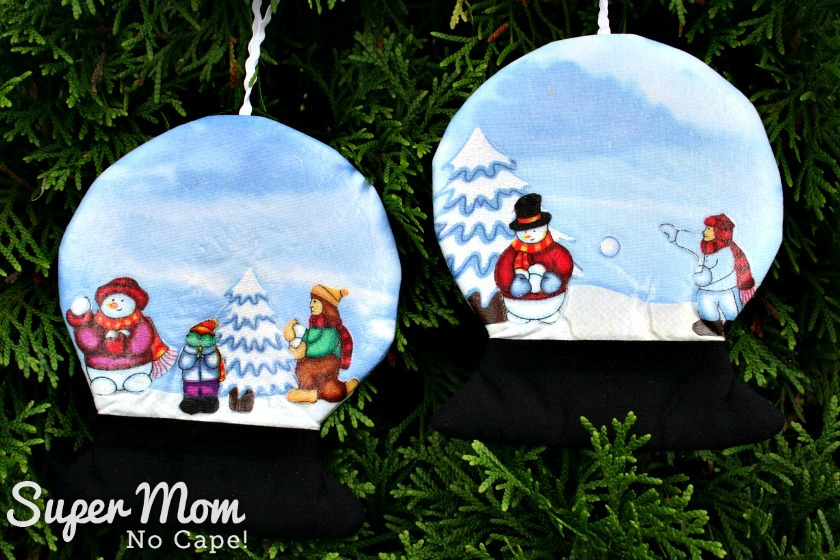 Sides switched of snowglobes with snowmen and children having snowball fight